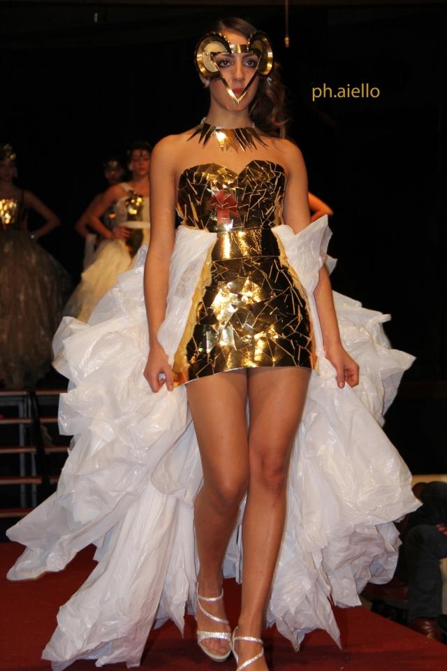 Una sensuale tunichetta dorata avvolge il corpo della modella impreziosito da un bianco velo che ne esalta le forme.